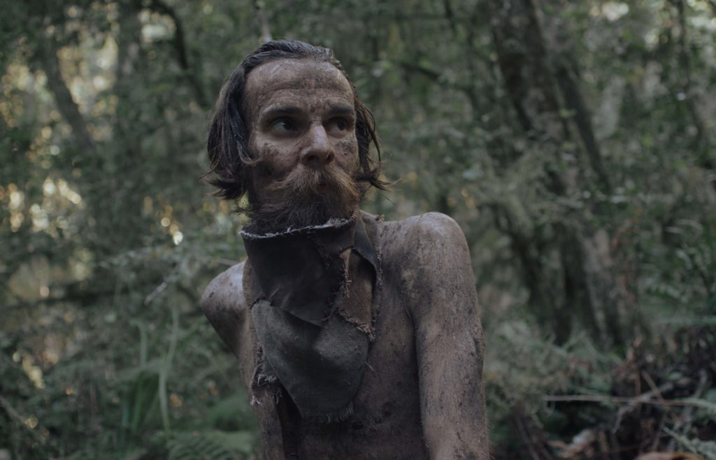 A skinny man covered in mud looks afraid or wary in a forest